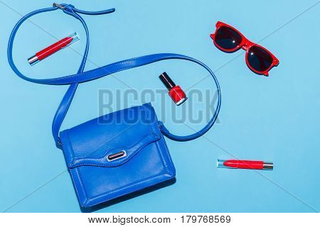 Stylish woman summer accessories in red and blue colors on colorful background