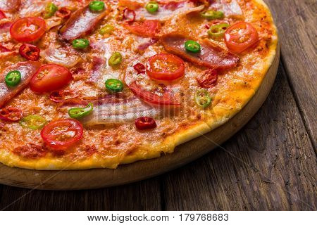 Delicious pizza with red and green hot chili peppers, bacon and cherry tomatoes closeup, thin pastry crust at wooden background, one piece cut off