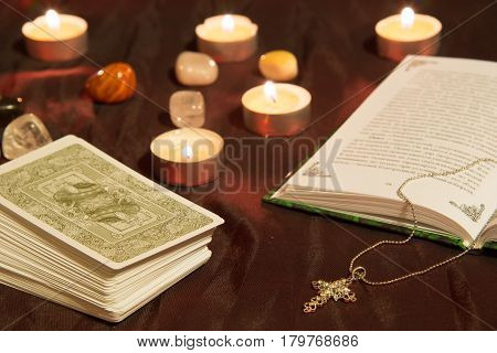 Moscow Russia - December 4 2016: Tarot card deck with book cross and candles. Esoteric background