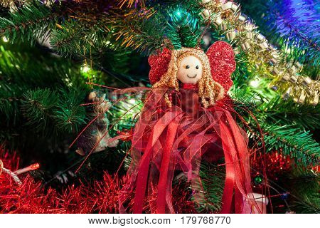 Cute Christmas tree red angel on a decorated Christmas tree