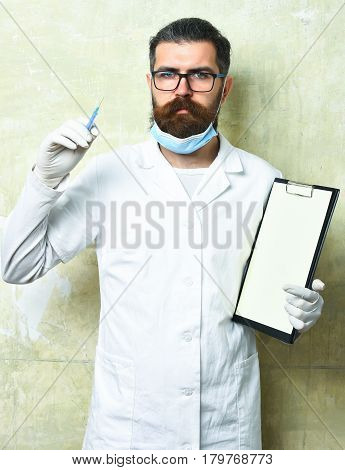 Bearded man long beard. Brutal caucasian doctor or unshaven hipster postgraduate student in medical gown gloves holding syringe and clipboard on texture studio background. Medicine concept poster