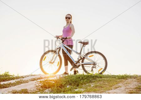 Girl with Bicycle on a background of sunrise