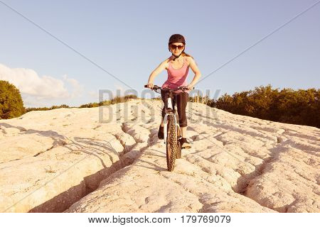 Young girl rides her bike down the hill.