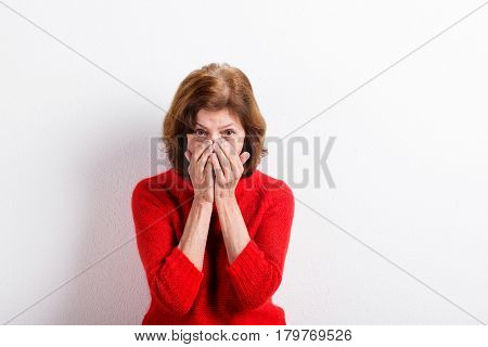 Beautiful senior woman in red woolen sweater, holding nose or head, having headache. Studio shot against white wall.