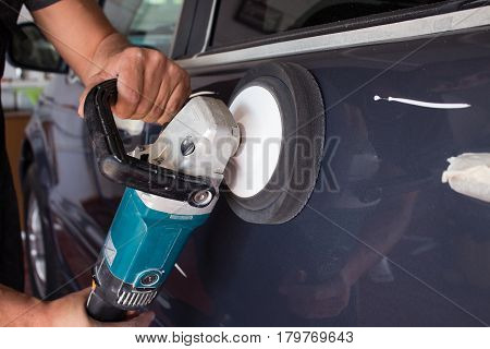 A man's hand holds a car polishing tool