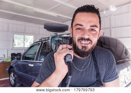 Man holds car polishing tool in the hands and smile