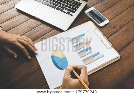 Business woman analyzing graph document with laptop and cell phone dark tone.