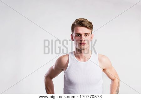 Young handsome hipster man in white sleeveless shirt. Studio shot on gray background.