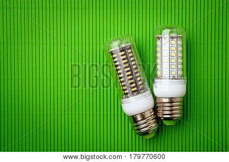 Energy saving LED light bulb on a green background with empty