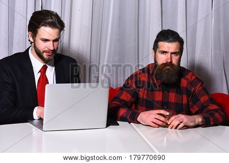 bearded men businessmen long beard brutal caucasian hipster with moustache hold glass with whiskey has serious and smiling face unshaven guys with stylish hair in suit and red tie with laptop