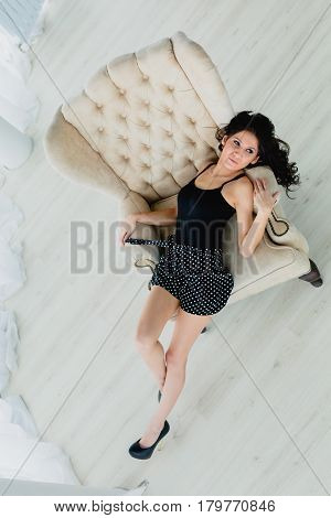 Slender brunette in black little dress lying on a white armchair