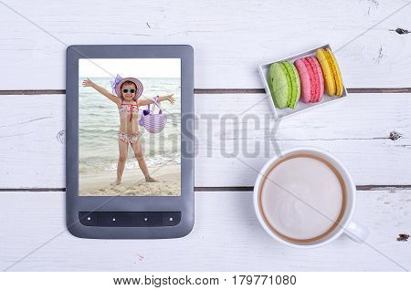 A tablet with a photo from a summer holiday and a cup of coffee on a wooden table. Modern gadgets on a white wooden background.