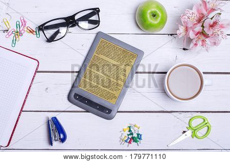 A Cup Of Hot Coffee, Glasses, A Notebook And An E-book On A Wooden White Background.