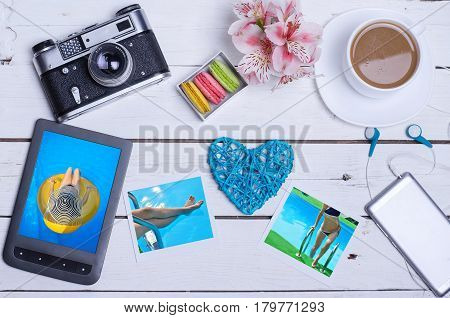Old photo camera tablet photos on a wooden table top view. The concept of summer recreation a cup of hot coffee on a wooden background.