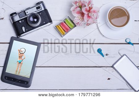 Old photo camera tablet smartphone headset on a wooden table with copy space. A cup of hot coffee and biscuits on a wooden table.