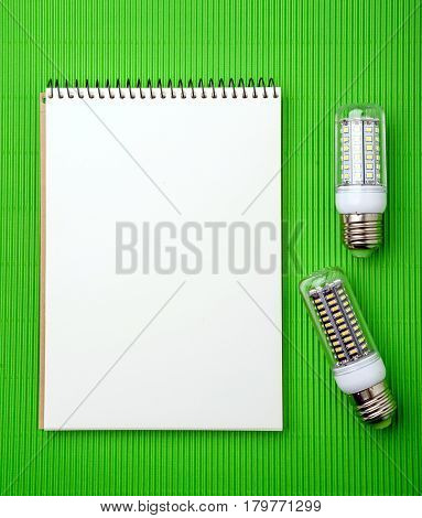 Energy saving LED light bulb with empty notepad on a green background