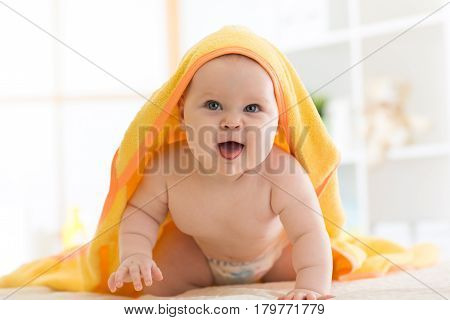 funny baby under the towel after bathing at home