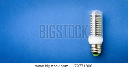 Energy saving LED light bulb on a blue background with empty space
