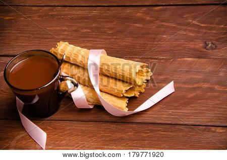 tubular wafer. hot chocolate. waffles on wooden boards