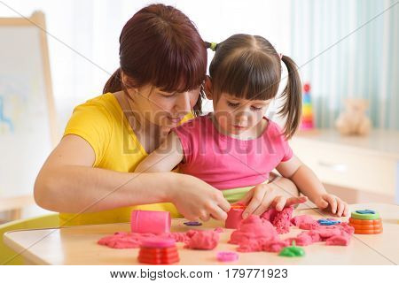 Cute child and mother playing with sculpting toy at home. Little girl building sandcastle.