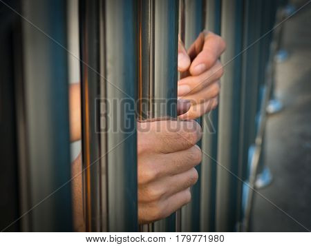 Hand of prisoner holding prison bars in jail.