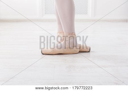 Ballerina legs third position in pointe, ballet dancer closeup background
