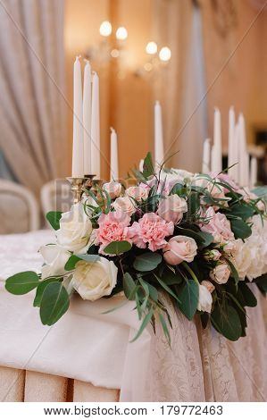 Wedding table decoration in the tenderly light pink style with roses, carnations and candles for the fiance and fiancee