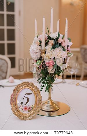 Wedding table decoration with the white and pink roses, carnations and candles for the guests