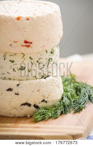 Variety of home made cheese and herbs on a wooden board. brined curd white cheese on the table.