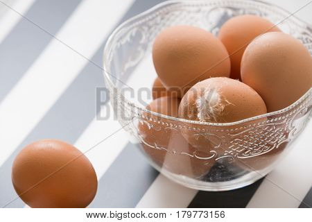 Fresh light brown organic eggs in a cristal bowl ready for Easter.