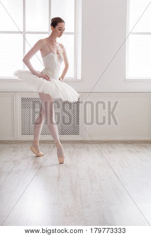 Classical Ballet dancer side view. Beautiful graceful ballerina practice ballet positions in tutu skirt near large window in white light hall.