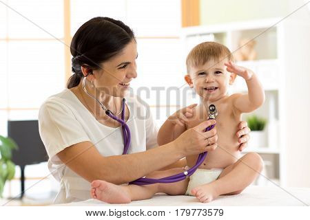 woman pediatrician examining of kid boy with stethoscope