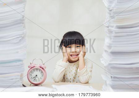 Little asian cute girl doing homework. big burden on students. overloaded child