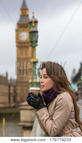 Girl or young woman drinking coffee in a disposable cup on Westminster Bridge with Big Ben in the background, London, England, Great Britain