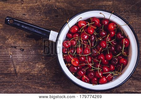 Red ripe juicy cherry in metal colander on rustic wooden background. Sweet summer berries. Freshly harvested merry. Directly above. Top view. Copy space.