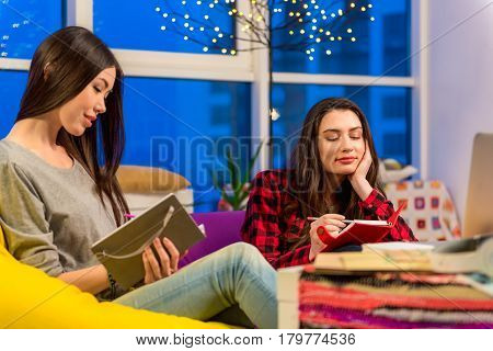 Focus on two attractive pensive asian and caucasian females. They noting in dairies while sitting in apartment. Muse concept