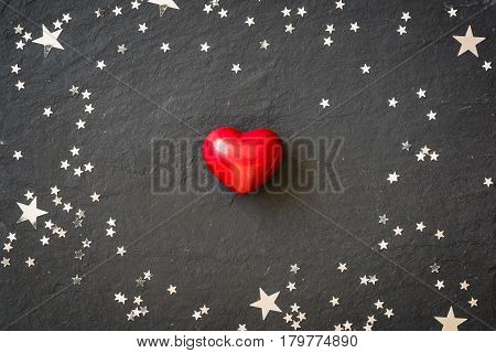 Small red heart on the black background with silver stars. Hearts and stars on a black board. Background. Valentine's and Christmas.