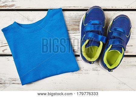 T-shirt and sneakers on wood. Achieving useful goals.