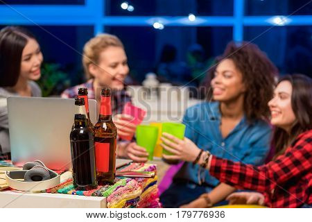 Focus on bottles of beer locating near laptop. Happy women having party