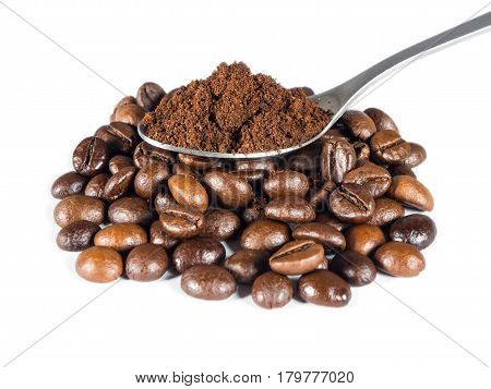 Spoon with ground coffee over pile of roasted beans on white isolated background