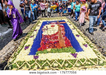 Antigua, Guatemala - March 26 2017: Locals admire flower & dyed sawdust procession carpet of Jesus during Lent in colonial town with most famous Holy Week celebrations in Latin America.