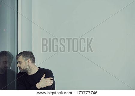 Man Sitting Against A Wall