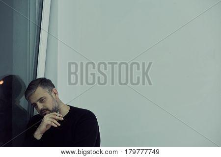 Man Smoking Next To The Window