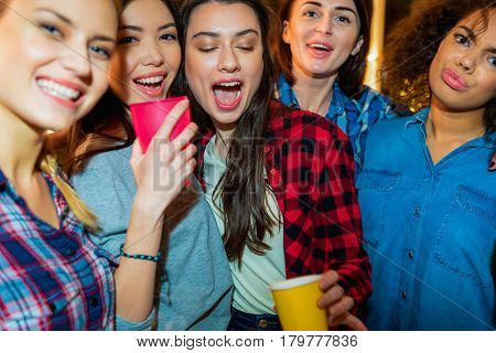 Focus on faces of outgoing young women at party. They drinking beverage
