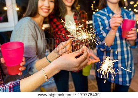 Focus on firework sparkler which smiling girls holding in arms. They celebrating birthday