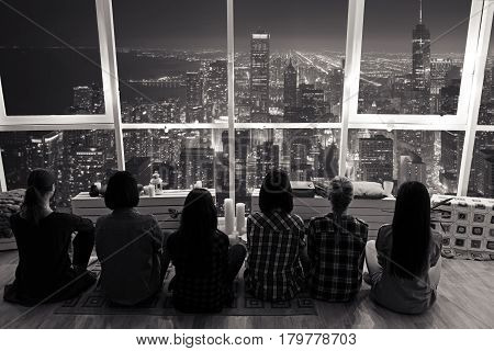 Top view of group of females watching at window. They admiring city landscape of Chicago. Beauty concept