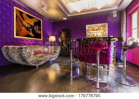 Spacious Interior With Upholstered Violet Walls