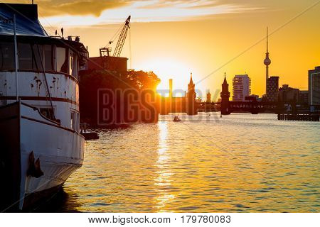 Berlin Skyline With Old Ship Wreck In Spree River At Sunset, Germany
