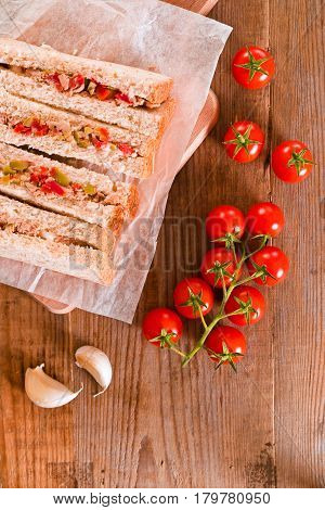 Tuna olives and tomato sandwiches on cutting board.