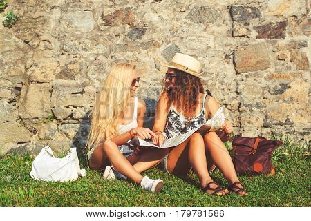 Two attractive woman tourists traveling on holidays in city smiling happy. Girls with city map in search of attractions.Summer vacation.